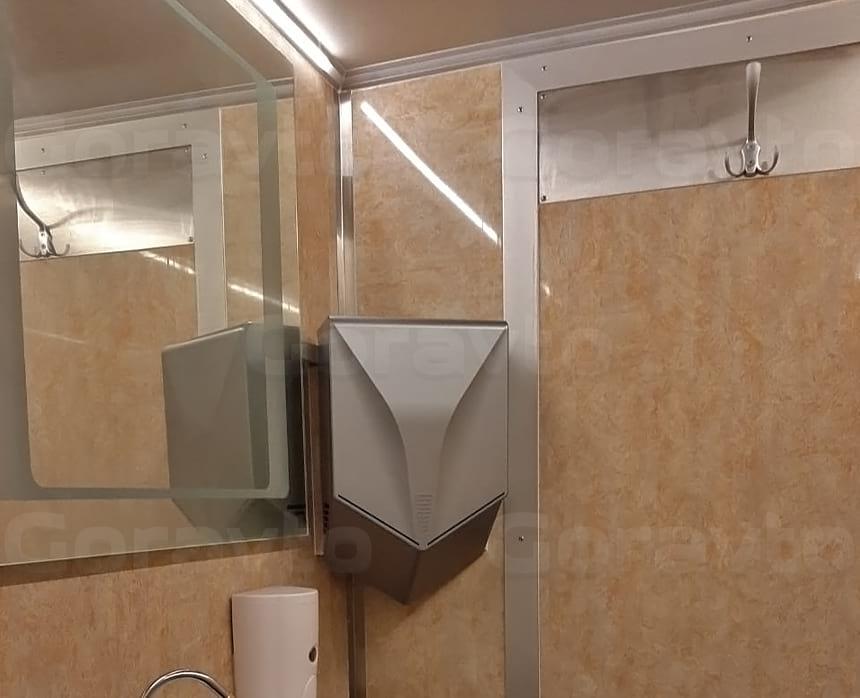 Размещение вешалки для одежды, раковины, дозатора мыла, зеркала и сушителя для рук в мобильном туалете